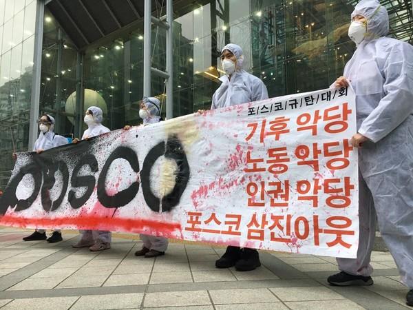 기후위기 비상행동이 지난 12일 포스코 주주총회가 열린 서울 강남구 포스코센터 앞에서 퍼포먼스 뒤 포스코 규탄대회를 하고 있다./ 기후위기 비상행동 제공